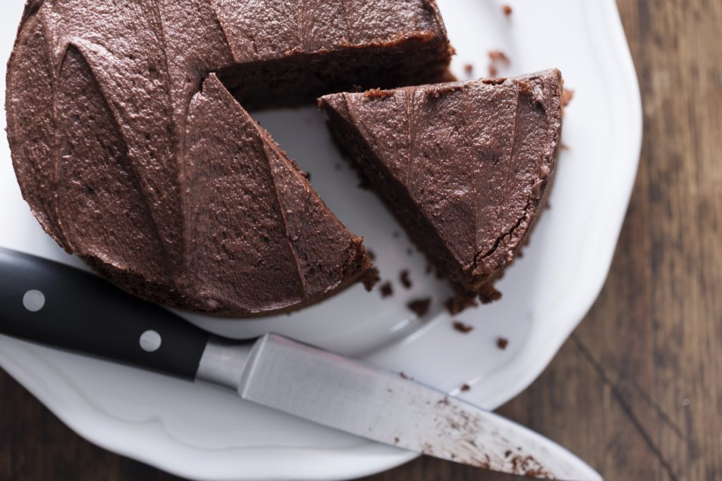 Whole Chocolate Cake on a white plate, with knife and piece sliced